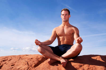 Muscular man meditating on red rocks Stock Photo