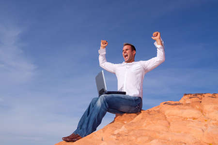 telecommute: Man celebrating his success in front of his laptop