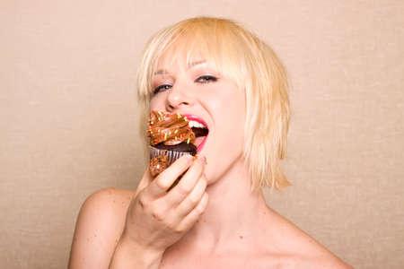 guilty pleasure: Mujer de comer un delicioso chocolate cupcake con escarcha de chocolate Foto de archivo
