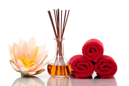 Spa towels and essential oils on white background