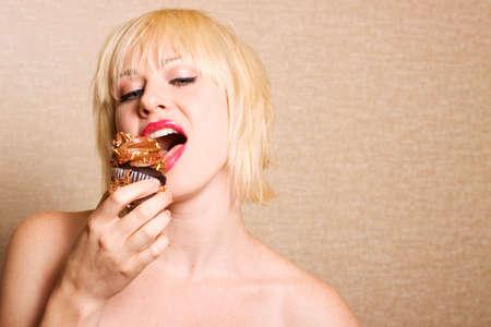 guilty pleasure: Mujer comer un delicioso chocolate cupcake con bizcochuelo chocolate