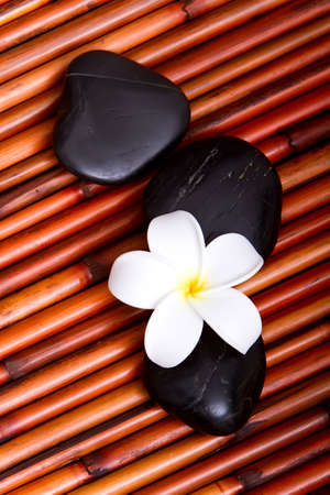 Hot spa stones and tropical frangipani flower on bamboo mat Stock Photo - 6966616