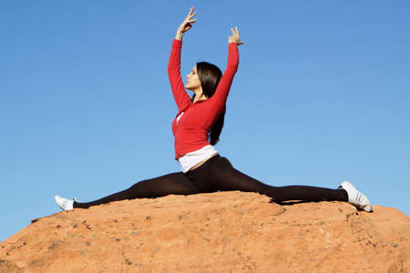 Gymnast doing split on red rocks 版權商用圖片