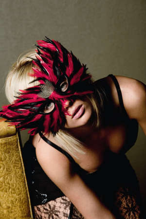 antique chair: Sexy blonde woman in carnival mask Stock Photo