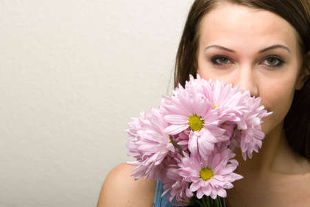 Pretty young woman smelling daisies photo