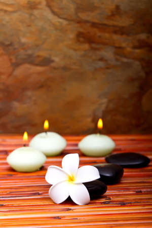 Hot spa stones, lit candles and tropical frangipani flower on bamboo mat photo