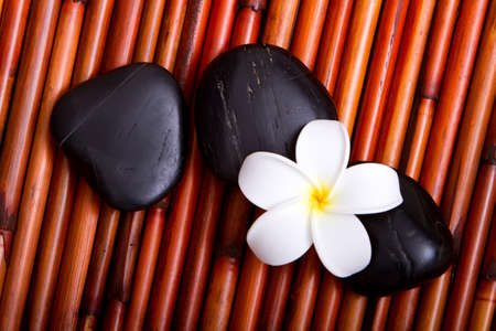 Hot spa stones and tropical frangipani flower on bamboo mat photo