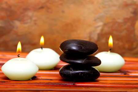Hot spa stones and lit candles on bamboo mat 스톡 콘텐츠