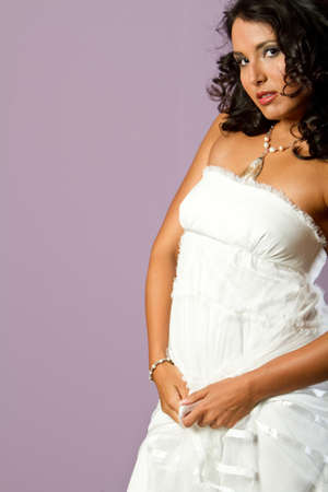 Gorgeous young ethnic girl in white dress studio shot photo