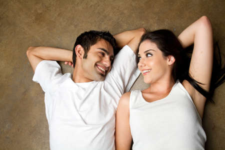 Young ethnic couple smiling to each other with love Banque d'images