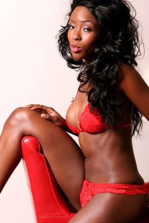 Sexy Afroamerikaner junge Frau, die mit erotischen roten Dessous Standard-Bild