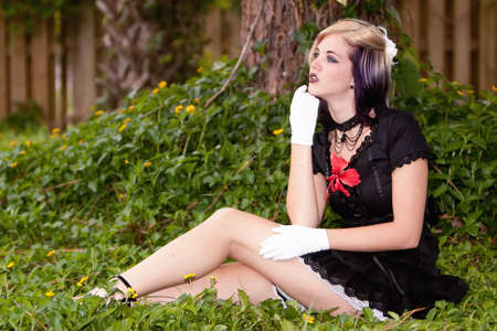 Gorgeous young woman sitting outdoors with alternative style outfit