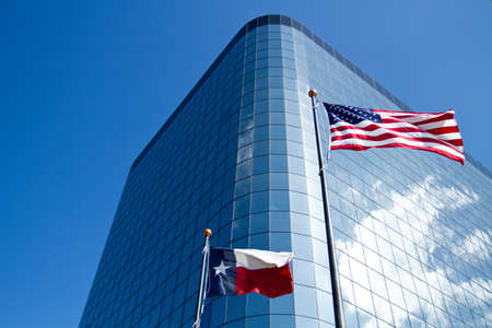 American and Texas flags front of an office building outdoor shot photo