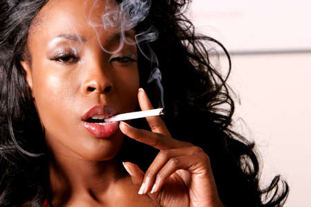 Sexy African American young woman smoking cigarette photo