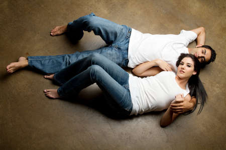 Sexy young multiracial couple in blue jeans relaxing on the floor Stock Photo - 7492726