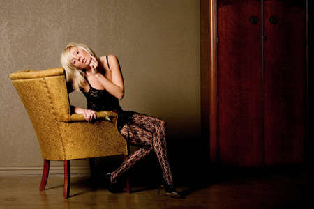 Sexy blonde woman on antique chair photo