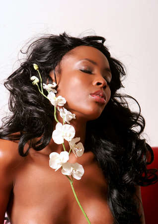 Gorgeous african american young woman holding white orchid flower on her face photo