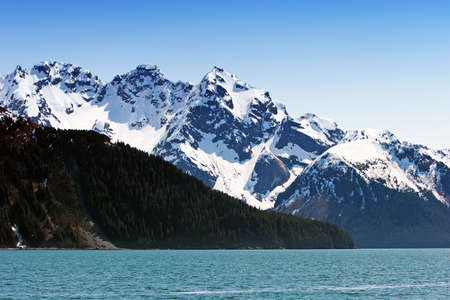 Snowy Alaska mountains by the water photo