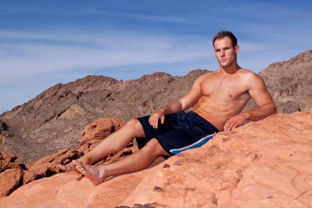 Athletic young man on red rocks photo