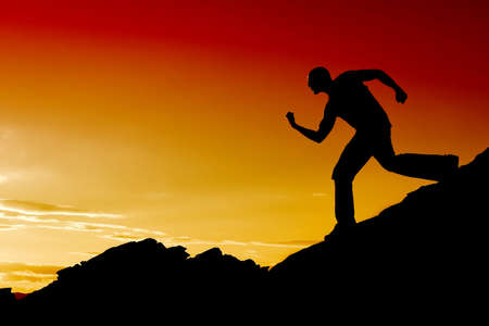 strong: Man silhouette running on mountain top Stock Photo