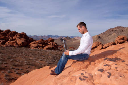 telecommute: Young man outdoors with his laptop