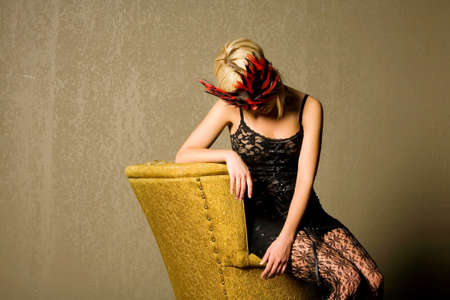 Sexy blonde girl with mask sitting on an old chair