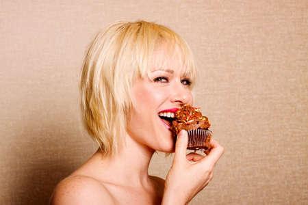 Woman eating eine köstliche Schokolade Cupcake mit Schokolade Zuckerguss