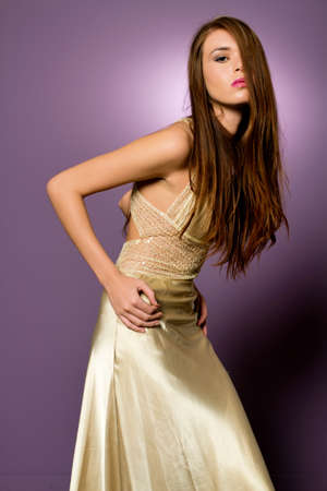 Beautiful young brunette girl with fashionable dress in studio
