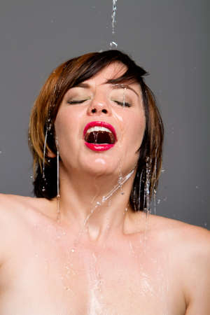 Gorgeous young woman with short hair under cold water photo