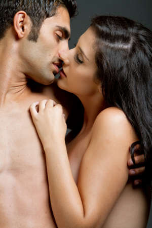 seductive expression: Young ethnic couple kissing each other Stock Photo