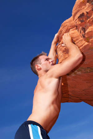 Athletic rock climber on red rocks photo