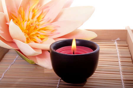 Spa candle and beautiful lotus flower for aromatherapy meditation photo