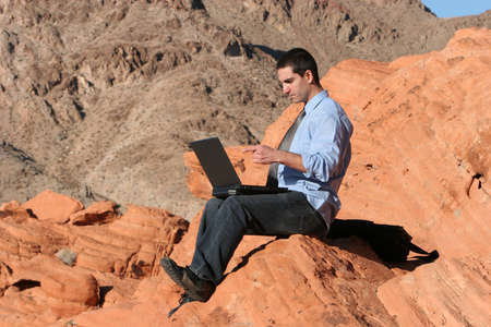 Businessman working on his laptop outdoors photo