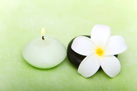 Spa stone, lit candle and tropical frangipani flower photo
