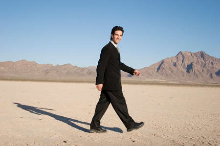 Businessman in drk suit walking photo