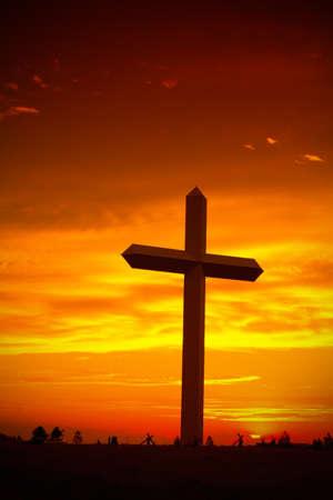 Enorme christelijke kruis silhouet tijdens zonsondergang tegen hemel