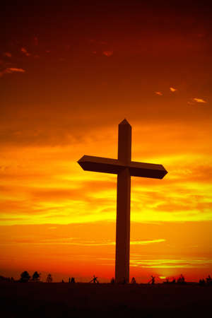 Huge christian cross silhouette during sunset against sky