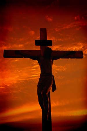 cruz religiosa: Silueta de la crucifixi�n de Jesucristo durante el atardecer contra cielo dram�tica