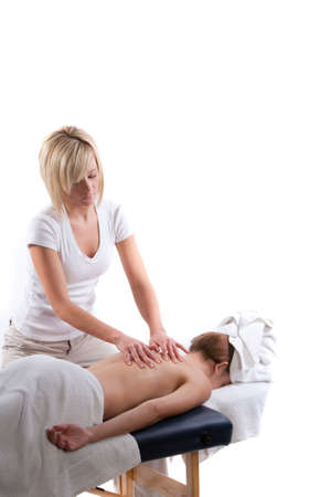 Massage therapist doing a back massage Фото со стока