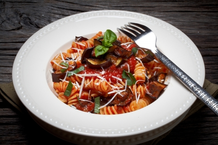 italian pasta fusilli with tomatoes,aubergine,ricotta cheese and basil. Фото со стока