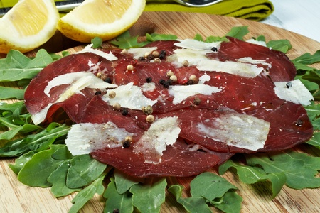 italian bresaola seasoned with flakes parmesan, olive oil an pepper served on a bed of rocket