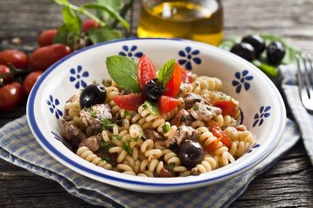 pez espada: Las pastas italianas Fusilli con el pez espada, el tomate de oliva y las materias primas Foto de archivo