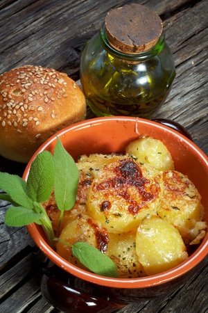 melted cheese: baked potatoes au gratin on a earthen bowl Stock Photo