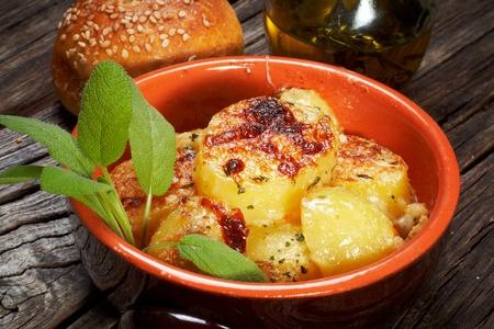 earthen: patate al forno gratinate su una ciotola di terracotta