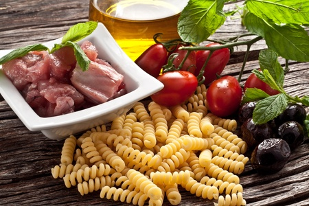 Italian Fusilli pasta with swordfish, olive and raw tomato ingredients photo