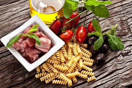 Italian Fusilli pasta with swordfish, olive and raw tomato ingredients Stock Photo