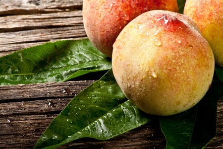 some fresh withe peaches with leaf on wood