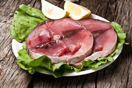 two slices of raw swordfish with lemon