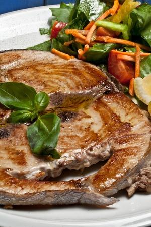 pez espada: pez espada cocinado y servido con ensalada de limón