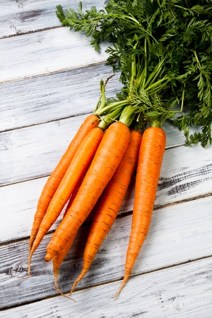 a fresh bunch of carrots on wood background photo